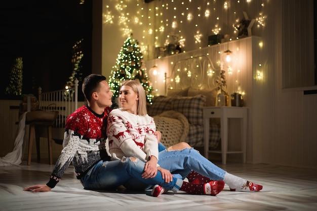 Coppia in maglioni a maglia vicino all'albero di natale. uomo e donna nella stanza interna di natale.