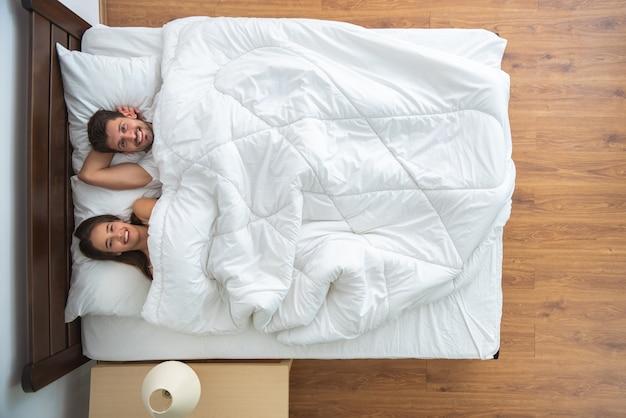 La coppia sdraiata sul letto. vista dall'alto