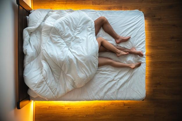 La coppia sdraiata sotto una coperta. vista dall'alto