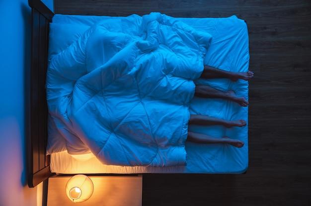 La coppia sdraiata sotto un piumone sul letto. sera notte, vista dall'alto