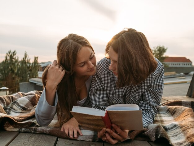 Coppia pone su un tetto a leggere un libro. auto-miglioramento della letteratura, tempo libero, hobby, concetto di topi di biblioteca