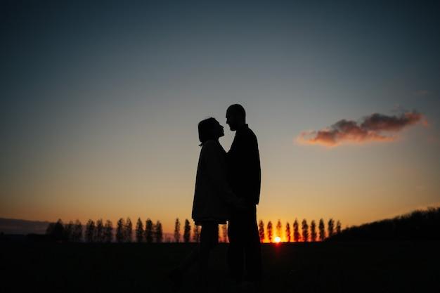 Coppia che si guarda e si tiene per mano al tramonto incredibile