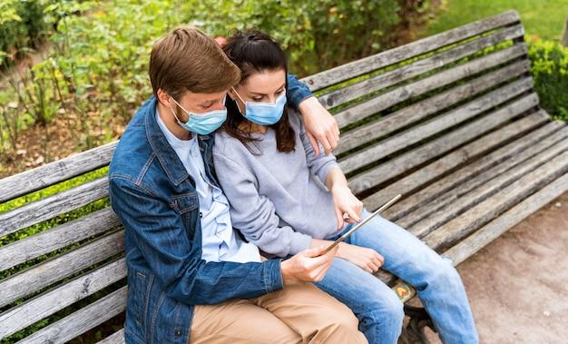 Coppie che esaminano una compressa mentre indossano maschere mediche