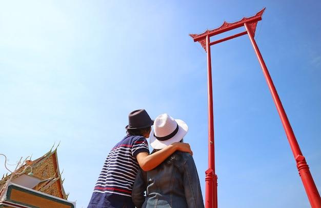 Coppia in cerca fino all'incredibile altalena gigante storica altalena in legno di teak precedentemente utilizzata nella vecchia cerimonia a bangkok in thailandia