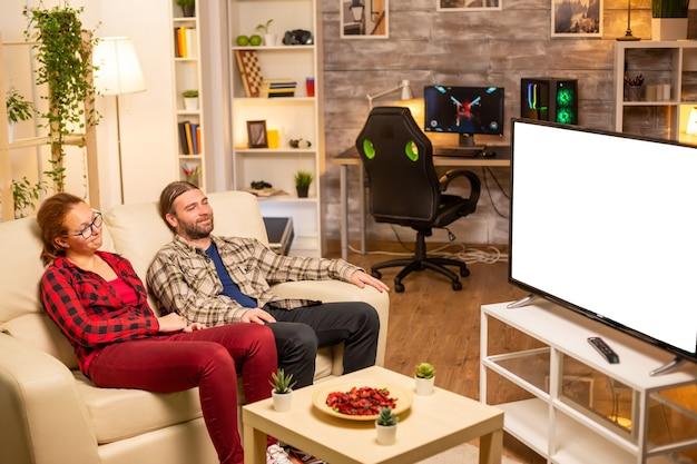 Coppia guardando lo schermo tv bianco isolato a tarda notte nel soggiorno.