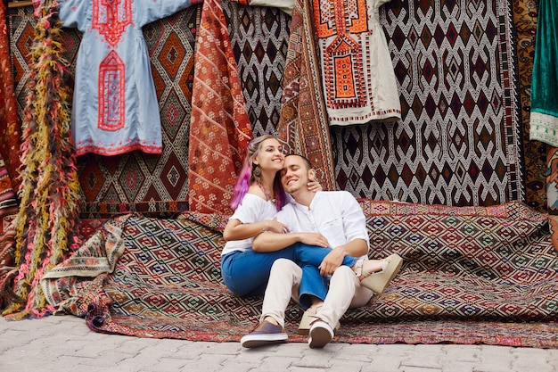 Coppia innamorata acquista un tappeto e tessuti fatti a mano in un mercato orientale in turchia. abbracci e volti allegri e felici di uomini e donne