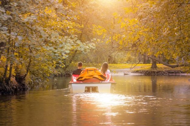 Coppia innamorata in un catamarano, bici d'acqua in un parco in autunno, tramonto.