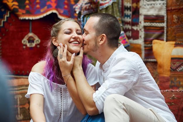 Coppia innamorata sceglie un tappeto turco al mercato. emozioni gioiose allegre sul volto di un uomo e di una donna. san valentino in turchia