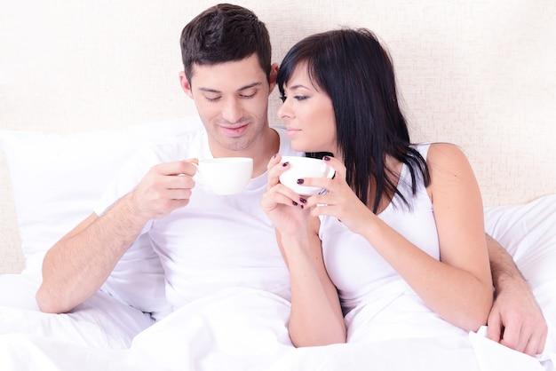 Coppia innamorata che beve caffè a letto