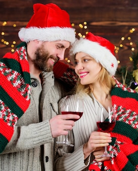 Le coppie innamorate si godono il vino rosso. data idilliaca. uomo donna cappelli di babbo natale allegro che celebra il nuovo anno. celebrazione di idee romantiche. buon natale. festeggiare insieme. festeggiando le vacanze invernali.