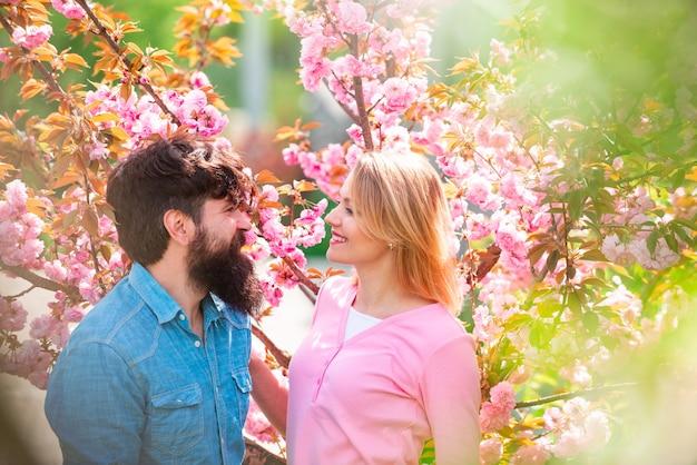 Coppia innamorata che si gode la giornata di sole nel parco durante l'albero in fiore di ciliegio
