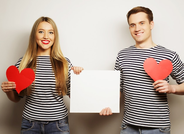 Coppia, amore e concetto di famiglia: coppia felice che tiene cuori in bianco e rossi bianchi.