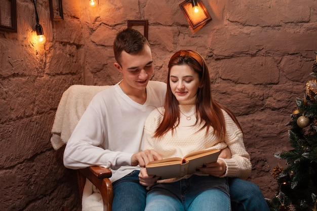 Una coppia innamorata, un ragazzo e una ragazza che leggono un libro. decorazioni natalizie.