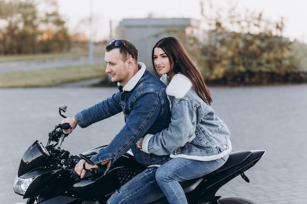 Una coppia innamorata, un ragazzo e una ragazza in sella a una motocicletta sportiva nera, al primo appuntamento
