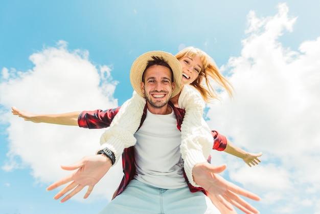 Coppia in amore divertendosi all'aperto - amici che giocano sulle spalle su un cielo blu