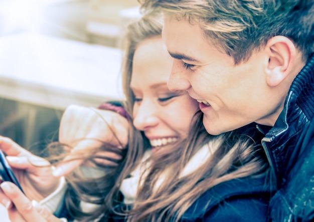 Coppia innamorata che si diverte con lo smartphone