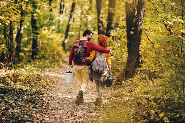 Coppia in amore che abbraccia e cammina nella natura. coppia in possesso di attrezzatura da picnic.