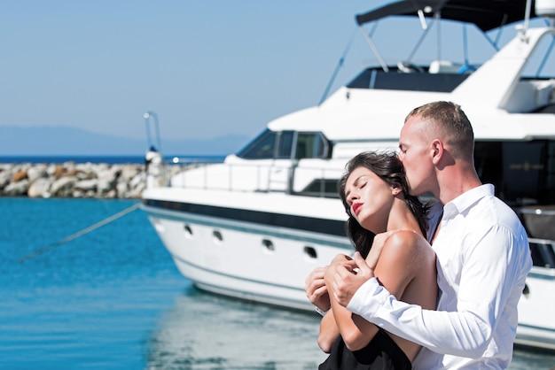 Coppia in amore abbracci e relax al molo vicino al concetto di vacanze estive yacht di lusso