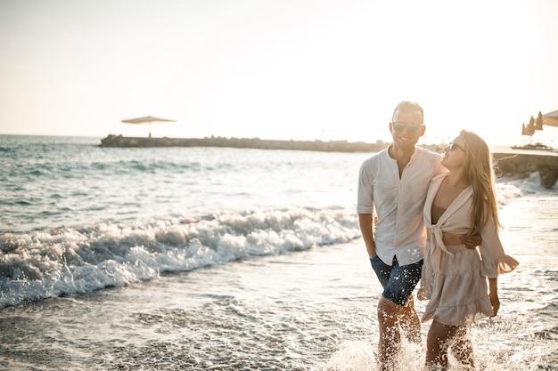 Una coppia innamorata sta camminando sulla spiaggia vicino al mare. giovane famiglia al tramonto in riva al mare mediterraneo. concetto di vacanza estiva