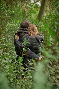 Coppia innamorata che si bacia da dietro nella foresta, tra le foglie degli alberi, indossano cappotti invernali.