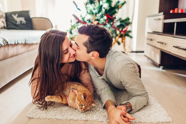 Coppia innamorata sdraiata vicino all'albero di natale e giocando con il gatto a casa