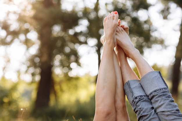 Coppia innamorata sdraiata sull'erba e alzando le gambe. giornata di sole estivo.