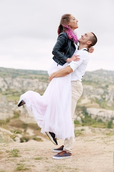 La coppia innamorata incontra l'alba nella natura, un uomo e una donna che si abbracciano e si baciano. bella coppia passeggiata romantica, stretto rapporto. colorazione creativa sulla testa delle ragazze
