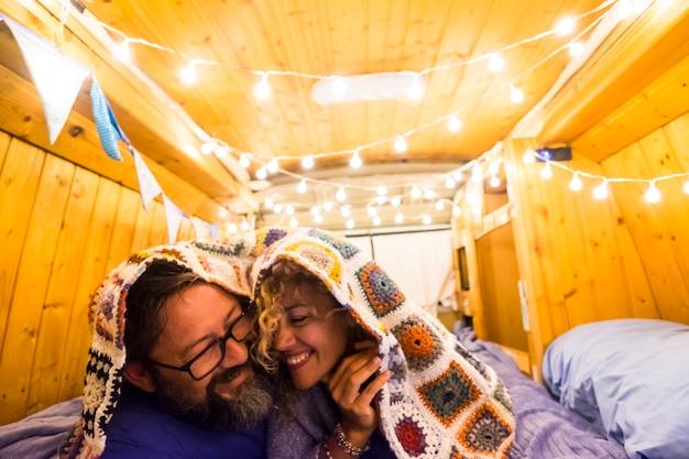 Coppia innamorata e relazione si divertono durante una vacanza di viaggio con un vecchio furgone restaurato in una piccola casa