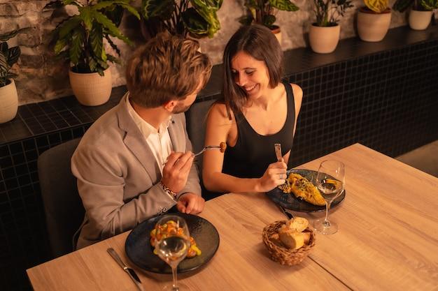 Coppia in amore in un ristorante, divertirsi cenando insieme al cibo, celebrando il giorno di san valentino, ripresa dall'alto