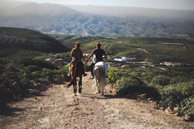 Coppia innamorata a cavallo di due bellissimi cavalli stare insieme in un'avventura di viaggio per uno stile di vita alternativo e una vacanza. concetto di viaggio di coppia per scoprire il mondo e il futuro