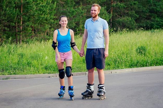 Coppia in amore con i rollerblade in estate nel parco. una donna giovane e attraente e un bell'uomo sui rulli