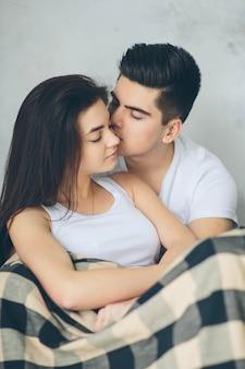 Una coppia innamorata si siede su una parete leggera. comprensione, amore e sostegno reciproci.