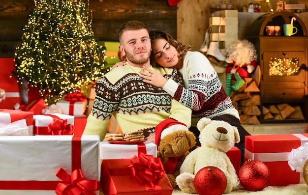 Coppia innamorata seduta accanto all'albero di natale. abbracciarsi tra le scatole presenti. coppia romantica si diverte. sera prima di natale. godendo trascorrere del tempo insieme a capodanno.