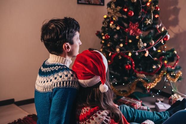 Coppia in amore seduto accanto a un albero di natale, con indosso il cappello di babbo natale e abbracci.