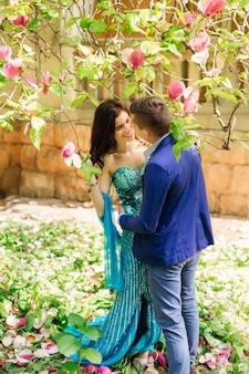 La coppia innamorata sta faccia a faccia sotto l'albero di magnolia