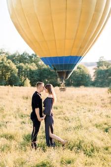 Coppia innamorata sta faccia a faccia, tenendosi per mano, in campo estivo con mongolfiera gialla