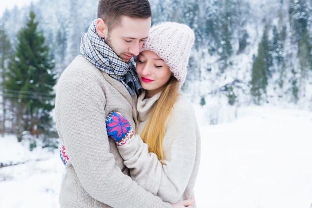 La coppia innamorata in maglioni abbraccia lo sfondo di una montagna ricoperta di boschi e neve