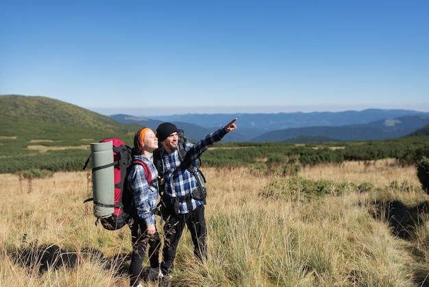 Coppia in amore turisti uomo e donna stanno su una pianura di montagna indicando con una mano lo spazio vuoto