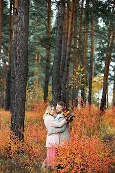 Coppia innamorata cammina attraverso la foresta autunnale. abbracci e baci di uomini e donne, relazioni e amore. la giovane coppia sta nell'erba rossa gialla, un mazzo di fiori in mano della ragazza