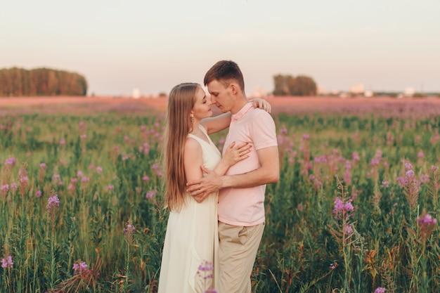 Una coppia innamorata cammina attraverso un prato fiorito. amore e fioritura primaverile. un uomo abbraccia una donna