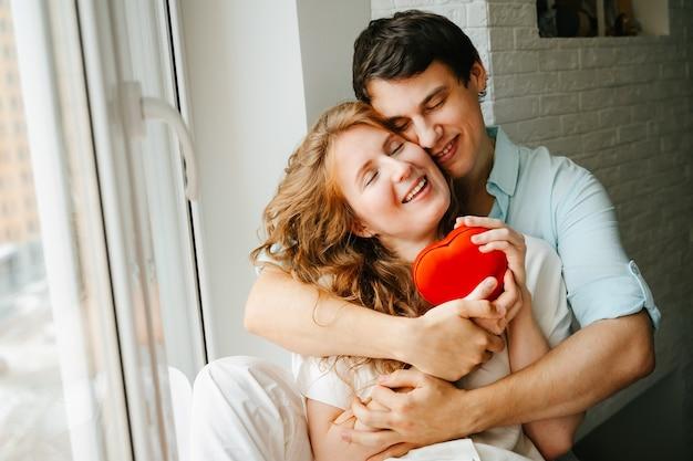 Coppia innamorata guarda una scatola regalo per il cuore durante le vacanze di san valentino.