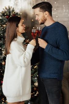 Coppia in amore con bicchieri di champagne vicino all'albero di natale a casa.
