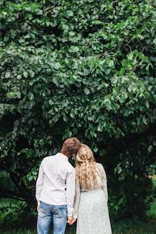 Una coppia innamorata, una ragazza e un uomo, in piedi nel parco, abbracci, incontro, baci, bouquet