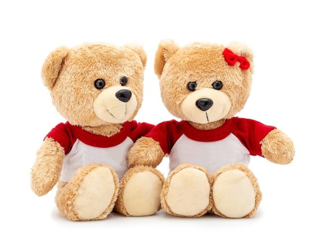 Coppia adorabile orsacchiotto marrone con maglietta e fiocco rosso isolato su uno spazio bianco