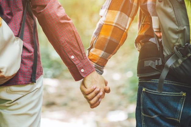 Amanti delle coppie che tengono le mani verso il sole con il chiarore luminoso del sole nei parchi