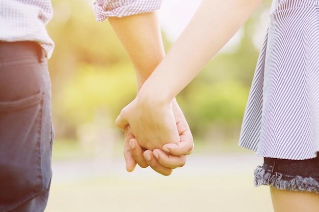 Amanti delle coppie romantiche che tengono le mani verso il sole
