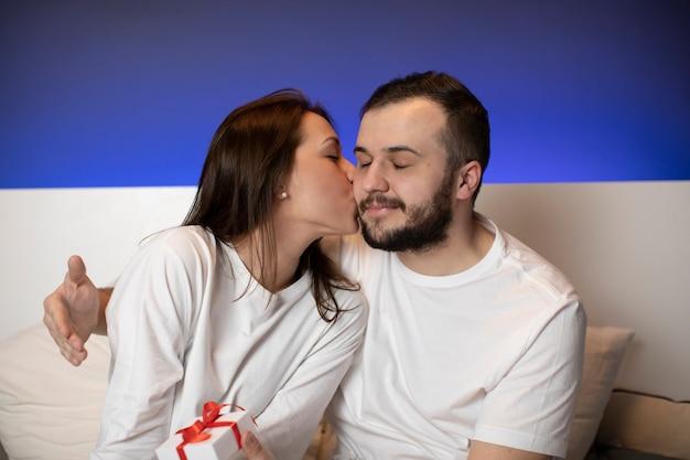 Coppia di amanti che indossano pigiami bianchi a letto