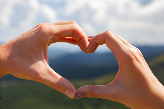 La coppia fa un cuore con le mani sullo sfondo del cielo.