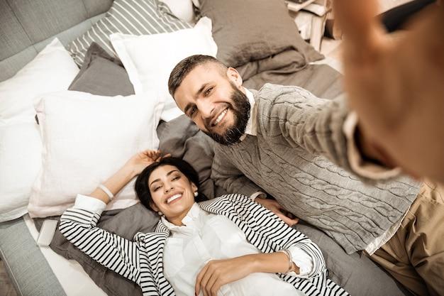 Coppie che fanno selfie. uomo di bell'aspetto contento con una barba rigogliosa mentre si fotografa con una moglie felice
