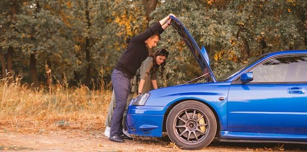 Un paio di maschi e femmine hanno dei problemi con la macchina durante il viaggio, riparare il controllo del motore